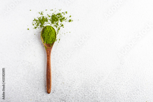 Foto wooden spoon with matcha tea green powder on white background