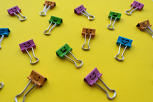 Multicolored Smiley Paper Clips Lie On A Bright Yellow Background