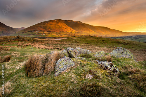 Obraz na plátně Beautiful Golden Light Shining Onto Mountains At Sunrise With Rugged Rocks In Foreground