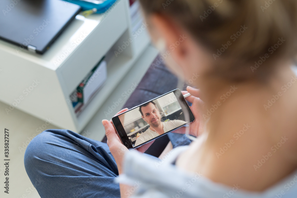 Fototapeta Stay at home, social distancing lifestyle. Woman at home relaxing on sofa couch using social media on phone for video chatting with her loved ones during corona virus pandemic.