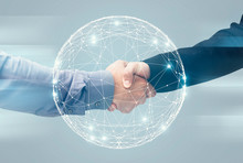 Two Unrecognizable Businessmen Handshaking Over Holographic Earth Globe, Double Exposure