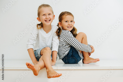 Fototapeta Happy siblings sitting close on a table with their legs up. Over white wall. obraz