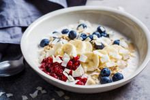 Overnight Oatmeal With Berries, Banana, Jam And Coconut In A White Bowl, Gray Background.