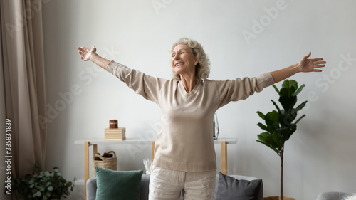 Fotografía Excited elderly mature retired woman dancing in living room with widely opened outstretched arms, enjoying freedom