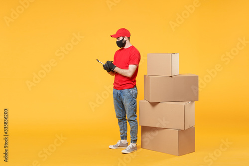 Cuadros en Lienzo Delivery man employee in red cap blank t-shirt uniform face mask glove hold empt
