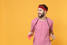 Cheerful Young Bearded Fitness Sporty Guy 20s Sportsman In Headband T-shirt Spend Weekend In Home Gym Isolated On Yellow Background. Workout Sport Motivation Lifestyle Concept. Hold Skipping Rope.