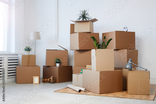 Fototapeta Minimal background image of cardboard boxes stacked in empty room with plants an