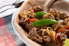 A Closeup View Of A Plate Of Beef Tibs, In A Restaurant Or Kitchen Setting.