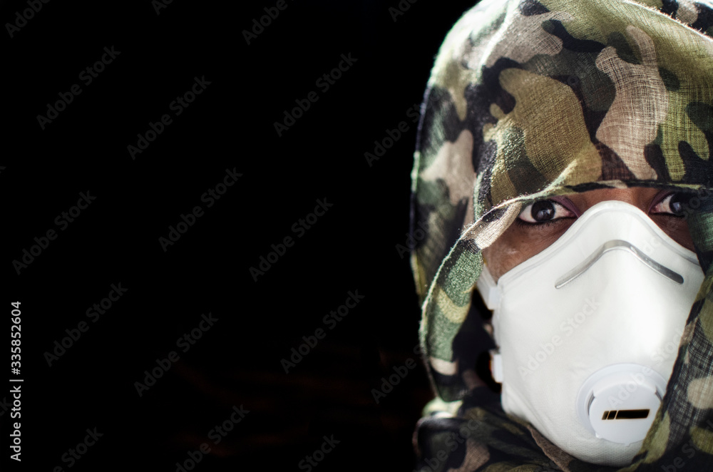 Fototapeta Conceptual photo of a warrior woman wearing a FFP3 mask and a camouflage head wrap.  Biological warfare. Coronavirus lethal weapon. Selective focus on her right eye. Black background. Copy space