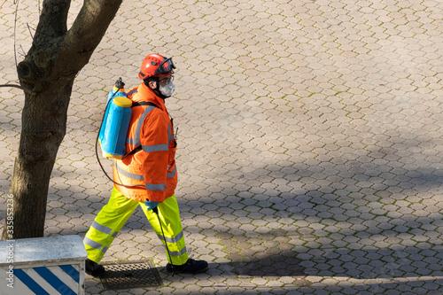 Photo trabajador fumigando la calle en tiempos del coronavirus ó fumigador ó desinfect