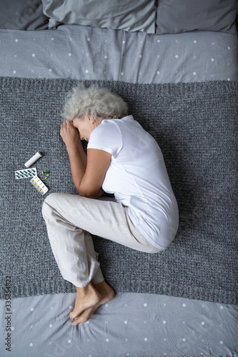 Fotografie, Obraz Above top view full length vertical image stressed elderly mature retired woman lying on bed in fetal position near medicament treatment, suffering from pain, depression or insomnia alone in bedroom