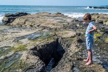 Boy On A Rocky Beach