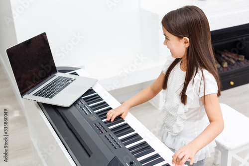Fototapeta Pretty young musician playing classic digital piano at home during online class
