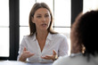 Close up confident serious businesswoman talking with business partner in office at meeting negotiation. Young female hr manager job introduction for diverse applicant at hire. Leader training concept