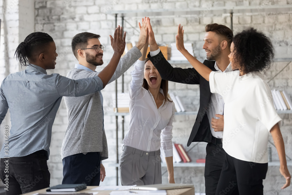 Fototapeta Excited successful multiracial business people giving high five, celebrating win. Good teamwork result concept. Happy employees team engaged in team building activity at corporate meeting.