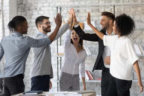 Excited successful multiracial business people giving high five, celebrating win. Good teamwork result concept. Happy employees team engaged in team building activity at corporate meeting.