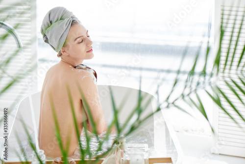 Fotografia Young woman with a towel on her head enjoys taking a bath, washes her body with