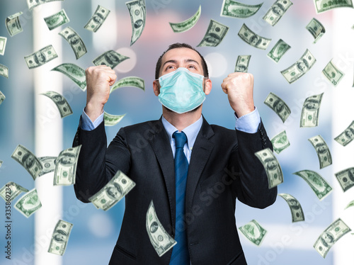 Fotografie, Obraz Businessman enjoying a rain of money while wearing a mask, coronavirus business