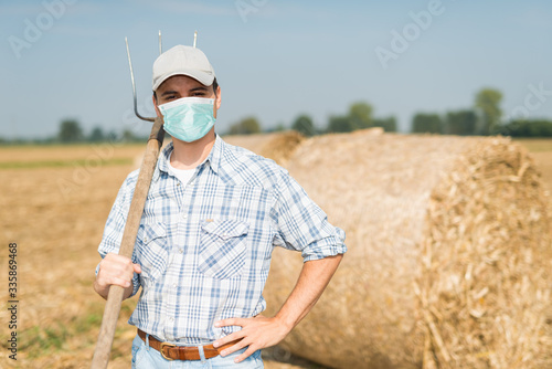 Photo Farmer in his field while wearing a mask, coronavirus pandemic concept