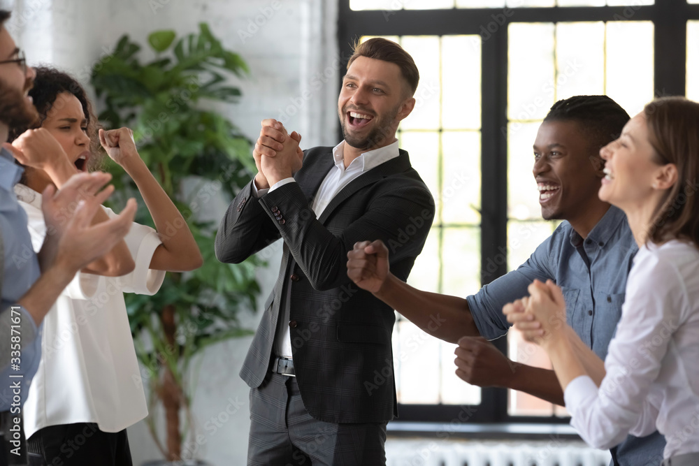 Fototapeta Happy businessman with team celebrate corporate victory together in office. Diverse overjoyed professional group rejoice company victory. Teamwork success win triumph concept at conference table.