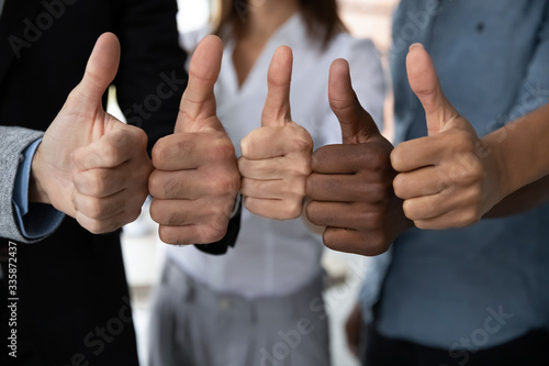 Close up view of diverse business team people hands showing thumbs up like finger gesture recommendation or good job choice Wallpaper Mural