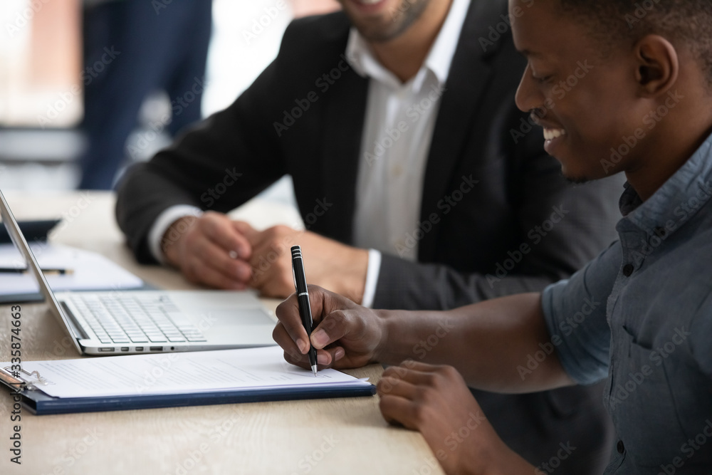 Fototapeta Close up happy african american businessman signing partnership agreement. Focused male on putting signature, concluding official contract with partner. Diverse man entrepreneur making profitable deal