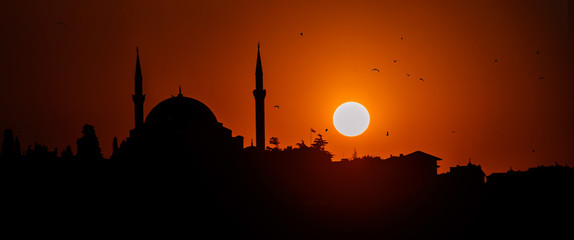 Panoramic silhouette of islam religion mosque at sun sunset twilight