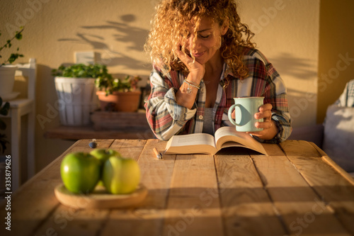 Fototapeta Beautiful curly adult woman read a book outdoor at home int errace or trendy room with wood table and tea or coffee - style lifestyle and concept of people enjoying life at home obraz