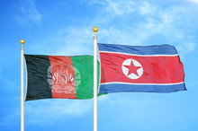 Afghanistan And North Korea  Two Flags On Flagpoles And Blue Cloudy Sky