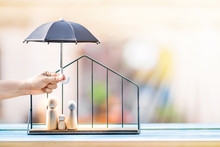 Woman Hand Hold Open The Black Umbrella For Protect To Family Wood Put In The House Model On Sunlight In The Public Park, Loan Or Saving Money For Property Protection  Real Estate And A Lover Concept.