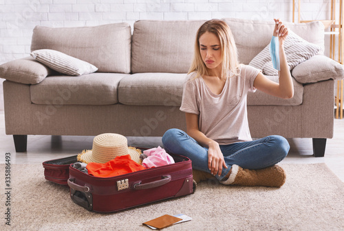 Photo Woman looks sadly at suitcase with clothes