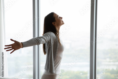 Fotografía Happy young woman stand near window breathe fresh air stretch exercise in bedroo