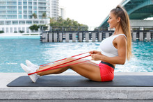 Fitness Woman Doing Resistance Band Exercise For Back Outdoors. Athletic Girl Working Out