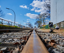 Low Angle Shot Along A Railroad Track Of A Railroad Line For Freight Trains In An Industrial Area In Berlin With The Focus In The Foreground.