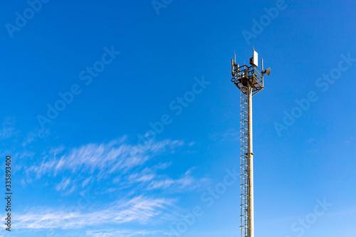 Fényképezés Communications tower with antennas against blue sky.