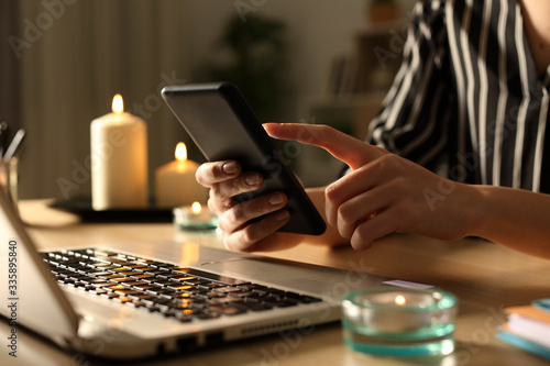 Valokuvatapetti Girl hands using phone on power outage with candles