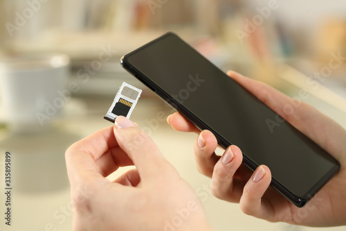 Fototapeta Girl hand inserting sim and sd card on smart phone obraz