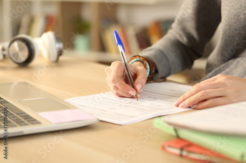 Fotomural Student hands filling out form document at home