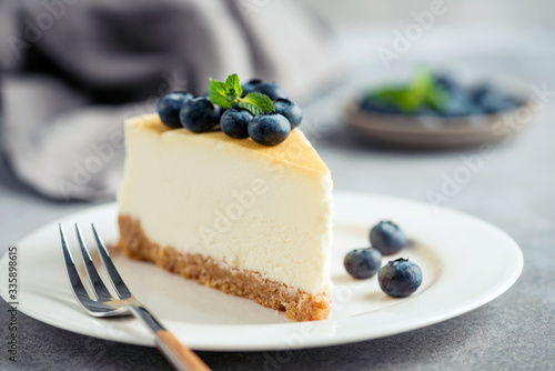 Fototapeta Cheesecake with blueberries on white plate. Toned image, selective focus obraz