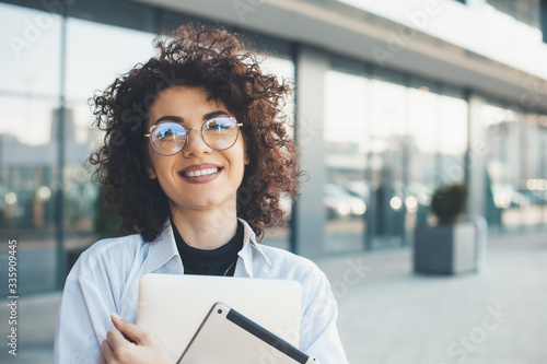 Close up portrait of a caucasian woman with curly hair and glasses holding a lap Poster Mural XXL