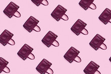 Beautiful Leather Purple Handbags On A Pink Paper Background  In Zine Style.