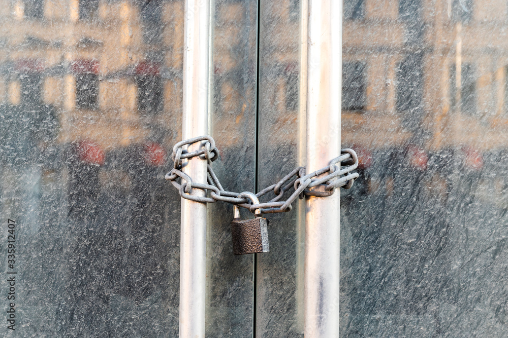 Fototapeta Lockdown shop market closed due to coronavirus pandemic door locked with chain. Bankruptcy of a business during long quarantine