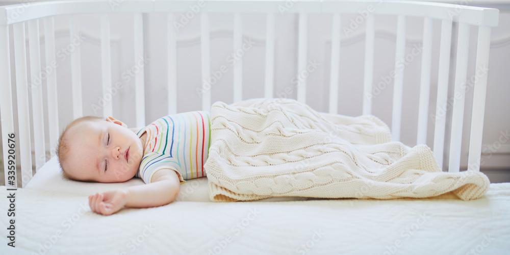Fototapeta Baby girl sleeping in co-sleeper crib
