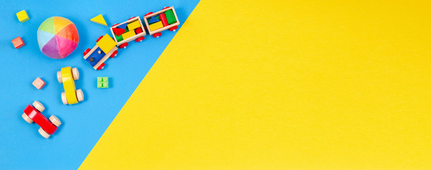 Baby kids toys background. Wooden train, toy car, colorful blocks on blue and yellow background