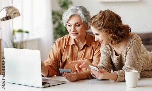Fotografia Young woman teaching senior mother to do online shopping.