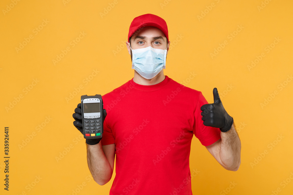 Fototapeta Delivery man in red cap blank t-shirt sterile mask gloves isolated on yellow background studio Guy employee hold bank payment terminal Service quarantine pandemic coronavirus virus 2019-ncov concept
