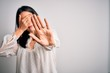 Young brunette woman with blue eyes wearing casual t-shirt over isolated white background covering eyes with hands and doing stop gesture with sad and fear expression. Embarrassed and negative