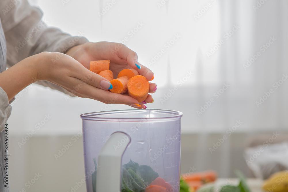 Fototapeta Woman blending carrot and other vegetables to make a healthy smoothie