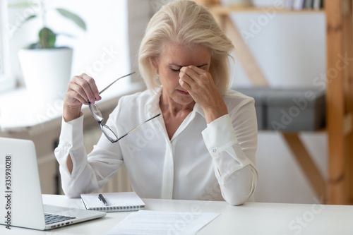 Slika na platnu Tired 60 years old businesswoman taking off glasses, suffering from dry eyes syndrome after long laptop use