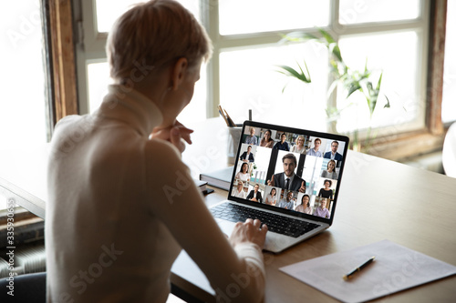 Rear view woman sit at desk learns new videoconference app online review, look at pc screen take part in group video call with corporate staff brainstorm distantly, study, work use modern tech concept - 335930655